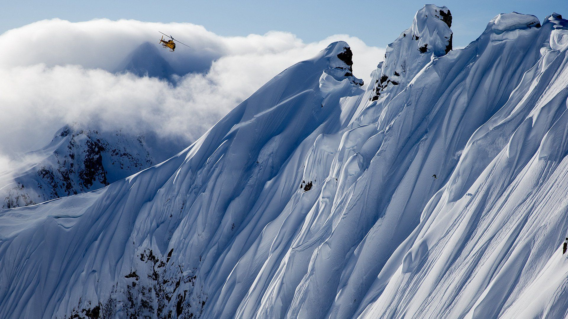 Dwarfed by huge, snow-covered, sheer cliffs near Juneau, Alaska, a member of the Legs of Steel group is barely visible skiing almost vertically downhill as a helicopter hovers above.